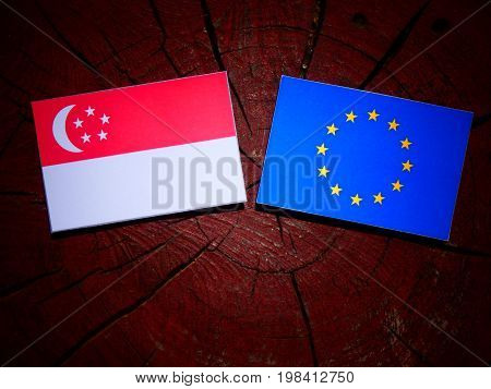 Singaporean Flag With Eu Flag On A Tree Stump Isolated