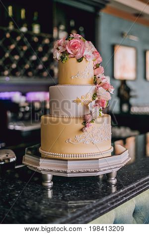 Multi level Wedding cake with roses on table
