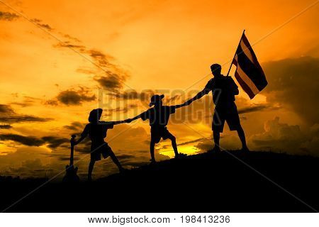 Scout leader holding Thai flag helping the boy scout hiking hill to success in silhouette sunset on camp.