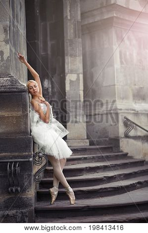 Vertical full length shot of a gorgeous ballerina leaning on the wall of an old castle posing gracefully on the stairs.