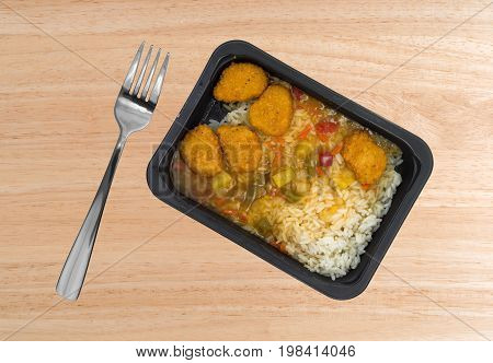 Sweet and sour chicken TV dinner with a fork to the side atop a wood table top.
