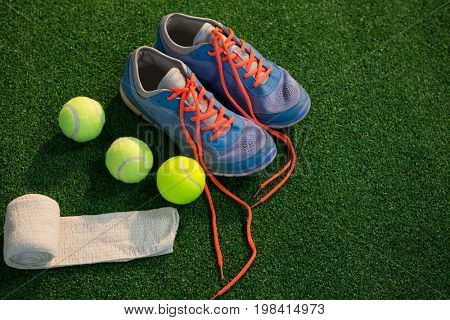 Sports shoes with tennis ball and napkin on field