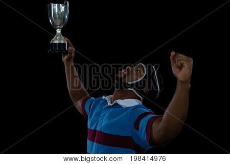 Happy rugby player holding trophy against black background