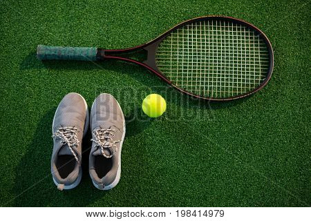 Overhead view of racket with tennis ball and sports shoes on field