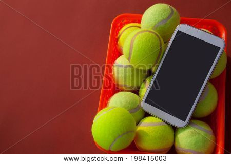 High angle view of mobile phone and tennis balls in basket on maroon background