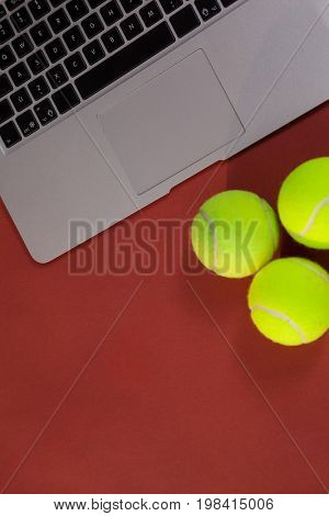 Overhead view of tennis balls by laptop on maroon background