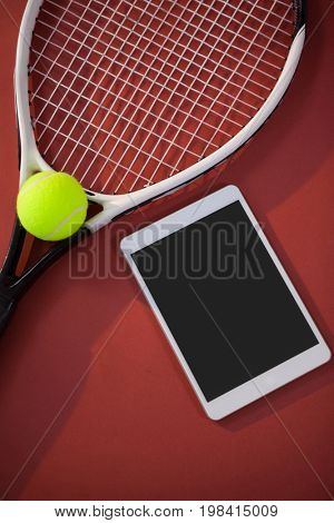 High angle view of tennis ball and racket by digital tablet on maroon background