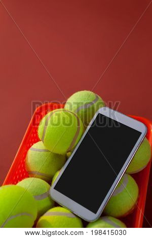 High angle view of smartphone and tennis balls in basket on maroon background