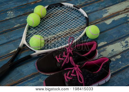 High angle view of black sports shoes by tennis balls and racket on blue wooden table
