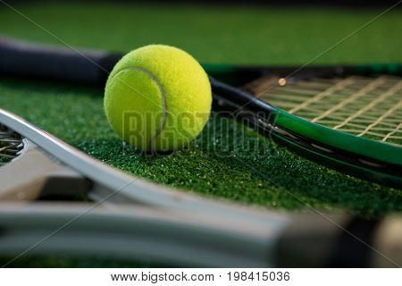 Close up of tennis ball with rackets on field
