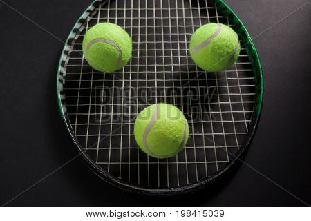 High angle view of balls on tennis racket against black background
