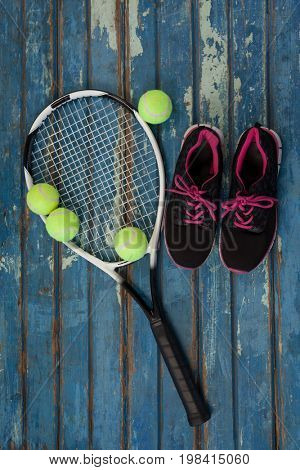 Overhead view of sports shoes with tennis racket and balls on blue wooden table