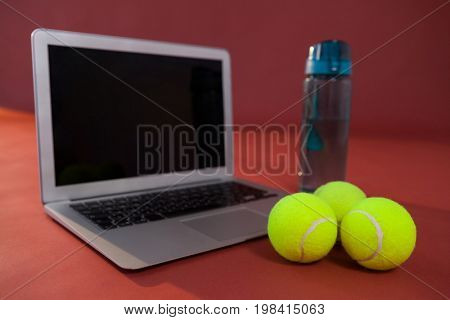 Close up of tennis balls by laptop and water bottle against maroon background