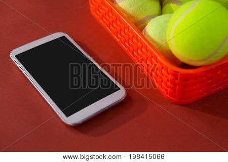 High angle view of tennis balls in red basket by smartphone on maroon background