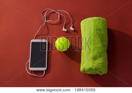 Overhead view of tennis ball amidst napkin and mobile phone with in-ear headphones on maroon background