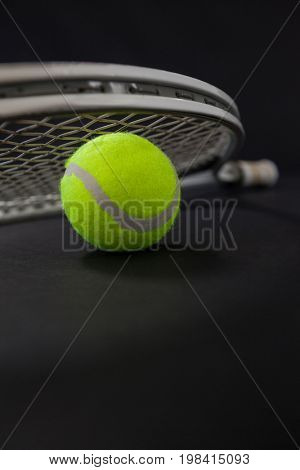 Close up of silver racket on tennis ball against black background