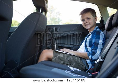 Portrait of teenage boy using laptop in the back seat of car