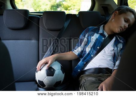Teenage boy sitting with football in the back seat of car