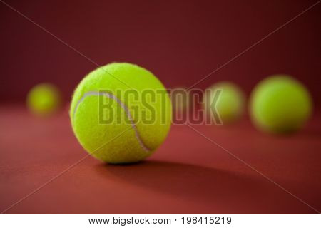 Close up of fluorescent yellow tennis balls on maroon background
