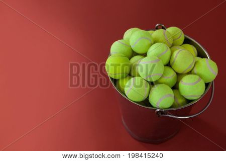 High angle view of fluorescent yellow tennis balls in metallic bucket against maroon background