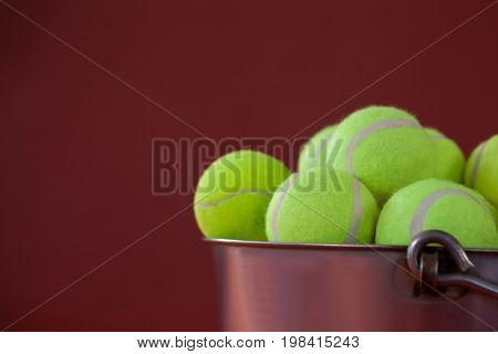 Close up of fluorescent yellow tennis balls in silver bucket against maroon background