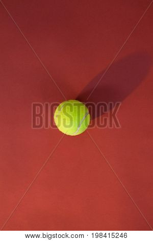 Overhead view of tennis ball on maroon background