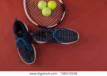 Overhead view of blue sports shoes by tennis racket and balls on maroon background
