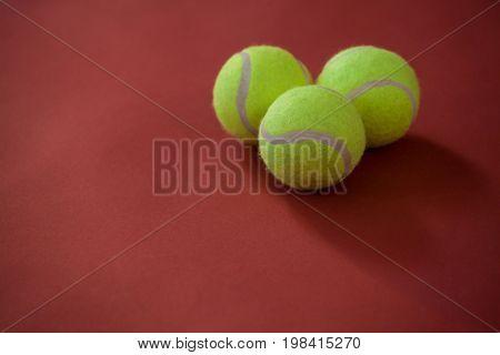 Close up of three tennis balls on maroon background