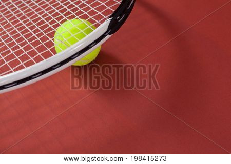 High angle view of white tennis racket with ball on maroon background