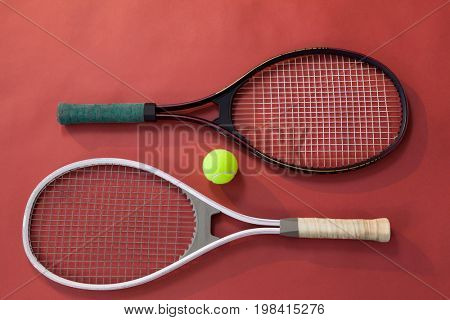 High angle view of ball amidst tennis rackets on maroon background