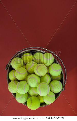 Overhead view of fluorescent yellow tennis balls in bucket over maroon background