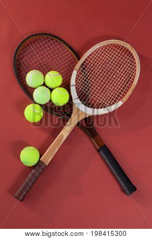 Overhead view of tennis balls with wooden rackets on maroon background