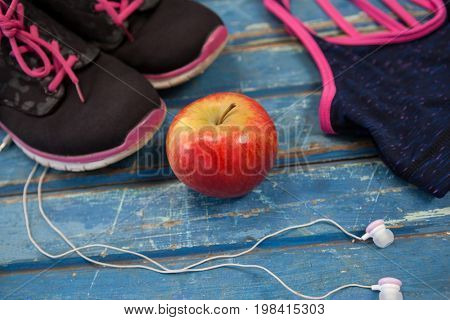 High angle view of womenswear with apple and headphones on wooden table