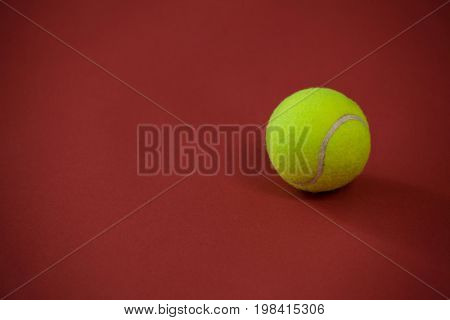 High angle view of tennis ball against maroon background