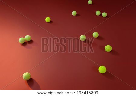 High angle view of fluorescent yellow tennis balls against maroon background