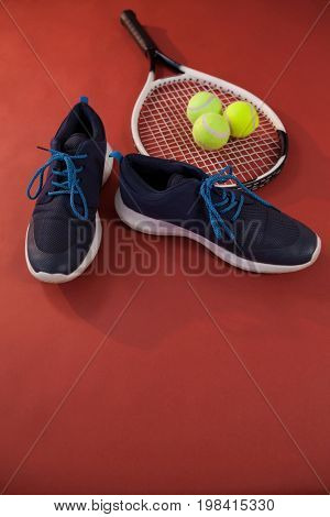 High angle view of blue sports shoes by tennis racket and balls on maroon background