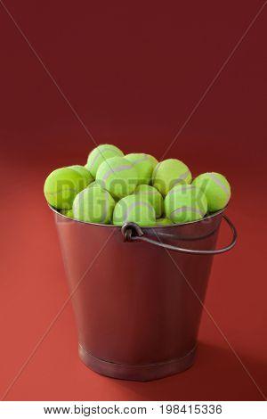 Fluorescent yellow tennis balls in silver bucket against maroon background