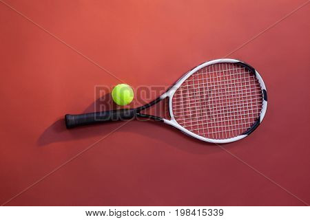 Overhead view of fluorescent yellow tennis ball on racket over maroon background