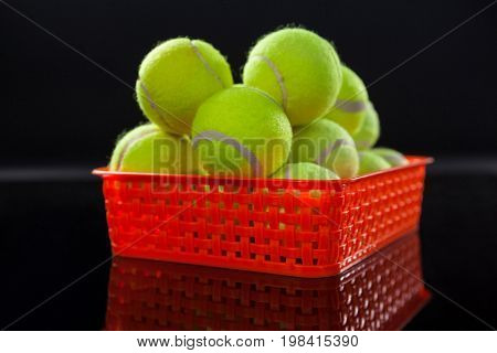 Close up of fluorescent yellow tennis balls in red plastic basket with reflection against black background