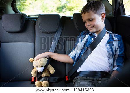 Happy teenage boy sitting with teddy bear in the back seat of car