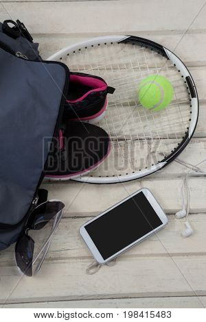 High angle view of gray bag on sports shoes with tennis gear by mobile phone and sunglasses over white wooden table