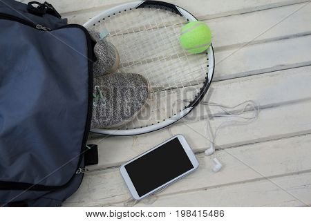 High angle view of gray bag on sports shoes with tennis gear by smartphone and over white wooden table