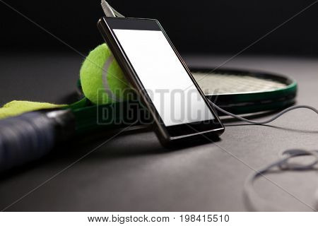 Close up of mobile phone and headphones by tennis ball with racket on black background