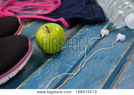 High angle view of womenswear with Granny Smith apple and headphones on wooden table