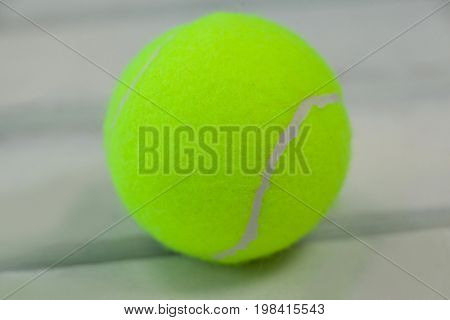 Close up of fluorescent yellow tennis ball on white wooden table