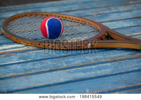 Close up of red and blue ball on wooden tennis racket over table