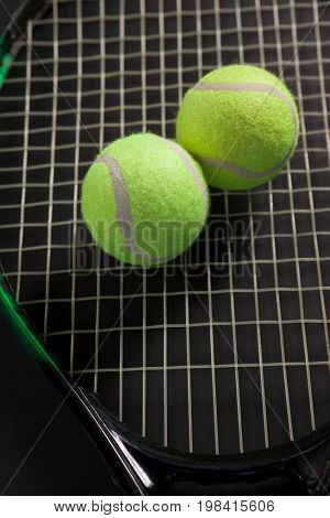 High angle view of tennis balls on racket against black background
