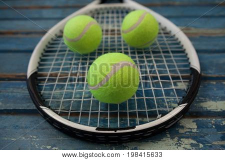 Close up of fluorescent yellow tennis balls on racket over blue wooden table