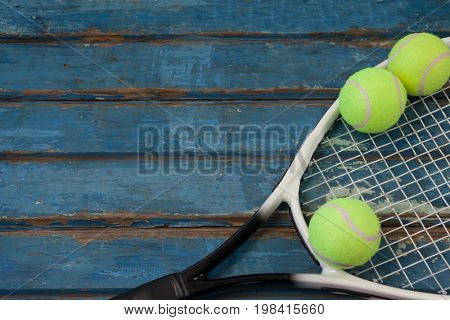 High angle view of tennis racket and balls on wooden table