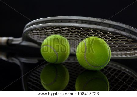 Close up of fluorescent yellow tennis balls with racket against black background